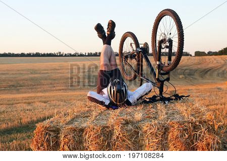 the cyclist with the bike resting on straw harvested field