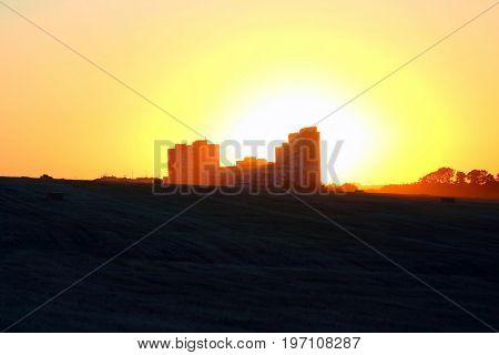 the silhouette of the house in field on sunset background