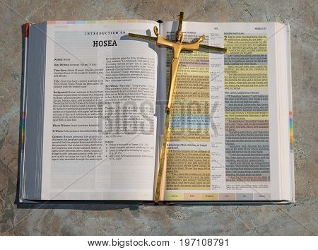 Bible opened to Hosea with Jesus on Cross