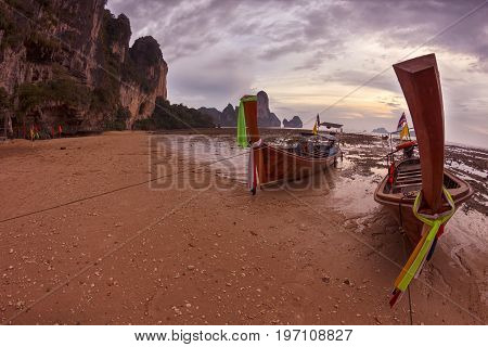 Epic view to traditional Thai longtail boats at the Railei beach during low tide at sunset