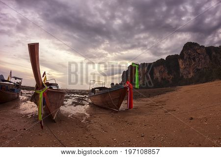 Traditional Thai longtail boats at the shore during low tide in pinkish sunset light