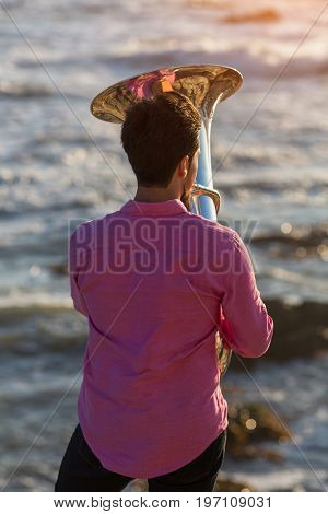 View from the back young musician play the trumpet on rocky sea coast during surf. Tuba instrument.