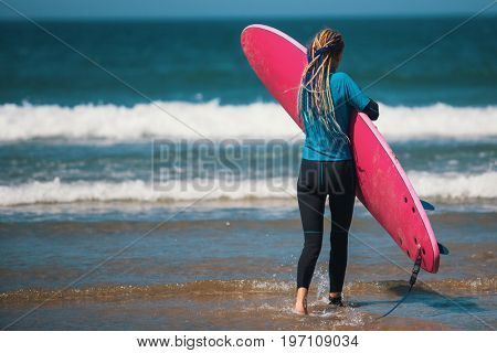 Young woman with surfboard at the ocean beach, view from the back.