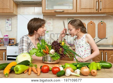 Mother and daughter cook and taste soup from vegetables. Home kitchen interior. Parent and child, woman and girl. Healthy food concept