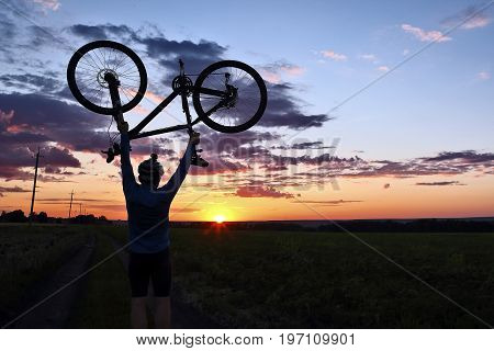 silhouette of a cyclist with arms raised up the bike at sunset