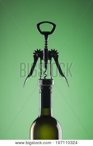 A bottle of wine with a stylish corkscrew for opening on a green background.