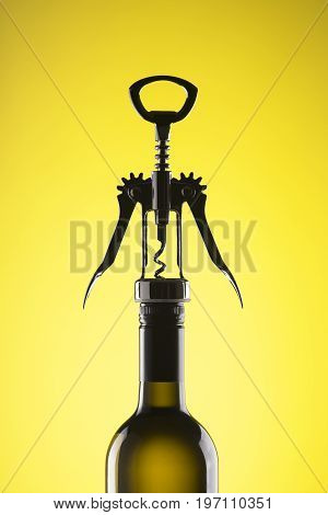 A bottle of wine with a stylish corkscrew for opening on a yellow background.