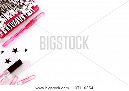 A mock up desk top styled photo in pink, black and white with a notebook, zebra print, stars, lipstick and paper clips on an isolated white background.