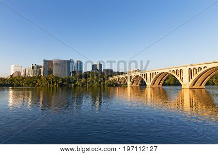 Sunrise over Potomac River with Key Bridge in a view. The bridge and urban skyscrapers as seen from Georgetown Park.