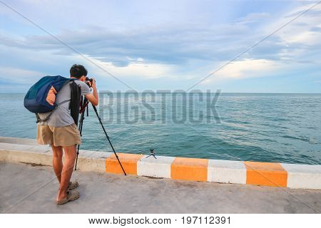 Man are taking a picture of the sea on the pier.