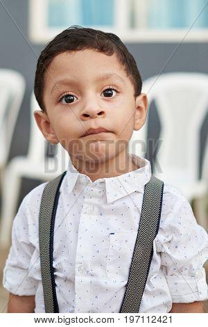 Portrait of hispanic boy in formal shirt. Close-up headshot of small latino boy