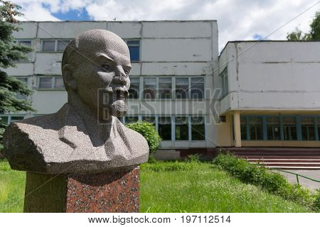 Photo of Old Lenin's bust against the background of the old Soviet building