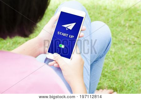 Top view of woman using her mobile phone with start up icon.