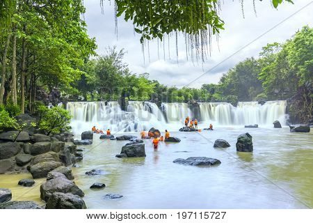 Dong Nai, Vietnam - June 25th, 2017: Beautiful waterfalls in Ecotourism with water flowing smooth as silk attract tourists to visiton a sunny summer day on weekends in Dong Nai, Vietnam