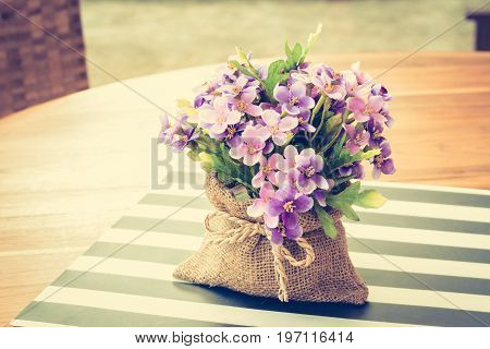 Purple flowers in small jute bag on the table - vintage style color effect with soft focus