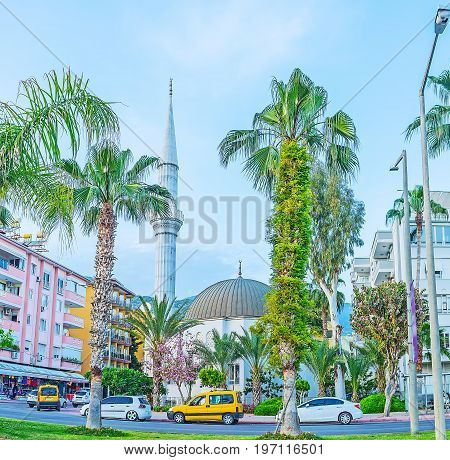 The mosque of Hasan Senli Saray is hidden among the palms and blooming trees of Ataturk boulevard in Alanya Turkey. poster