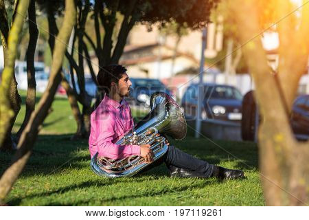 Musician instrumentalist with the tuba sitting on the grass in the Park.