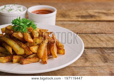 Homemade french fries serve with ketchup and sour cream or mayonnaise. Golden brown crispy french fries sprinkle with salt and oregano on white plate for snack or appetizer.French fries on wood table.