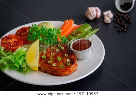 Barbecue pork steak on white plate served with barbecue sauce and vegetables. Pork steak for lunch or dinner on granite table. Moist and soft homemade pork barbecue with mash potato and vegetable.