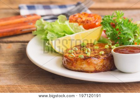 Barbecue pork steak on white plate served with barbecue sauce and vegetables. Pork steak for lunch or dinner on wood table. Moist and soft homemade pork barbecue served with mash potato and vegetable.Pork steak ready to serve on wood table.