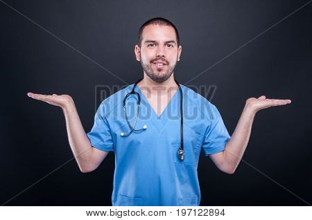 Doctor Wearing Scrubs With Stethoscope Holding Copypsace Both Hands