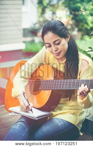 Asian Woman Playing Acoustic Guitar With Bright Sunlight. Vintage Effect Tone.