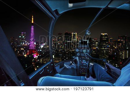 Helicopter flying over Tokyo tower and Tokyo cityscape view from skyline at night, Tokyo, Japan.