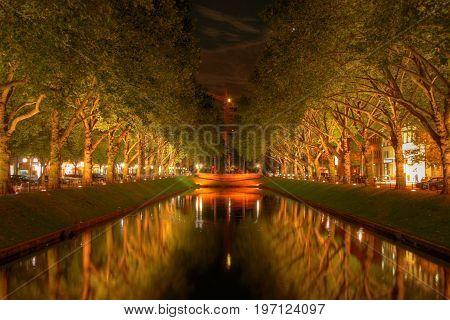 the konigsallee in dusseldorf is illuminated at night