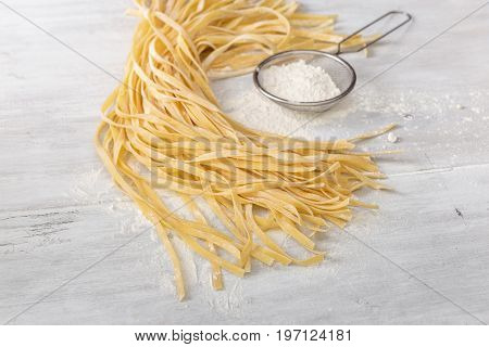 Raw homemade noodles with flour sieves on light rustic wooden table close up