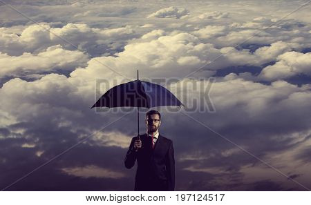 Businessman with umbrella standing over stormy background. Business, protection, crisis concept.