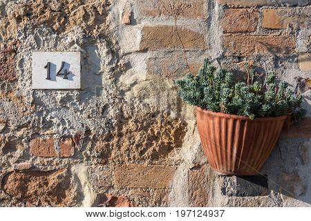 Road sign on a house reading the number fourteen made out of metalic digits on a marble base put on a stone and bricks wall. Sign is situated in the upper left hand part of the photo