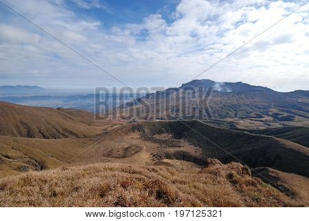 active and inactive volcano from view on top of a mountain in the mount Aso area in autumn Japan