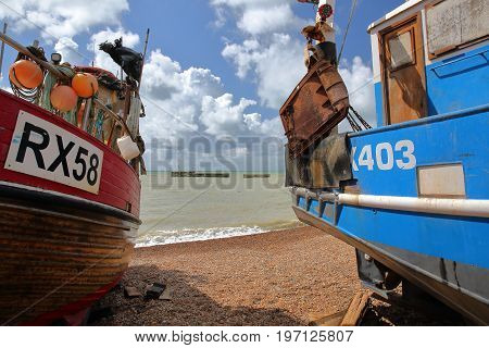 HASTINGS, UK - JULY 22, 2017: Beach launched colorful fishing boats with a beautiful sky