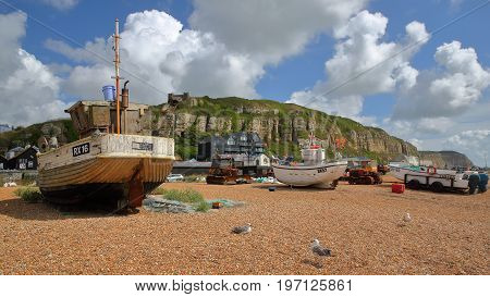 HASTINGS, UK - JULY 22, 2017: Beach launched fishing boats with East Hill in the background