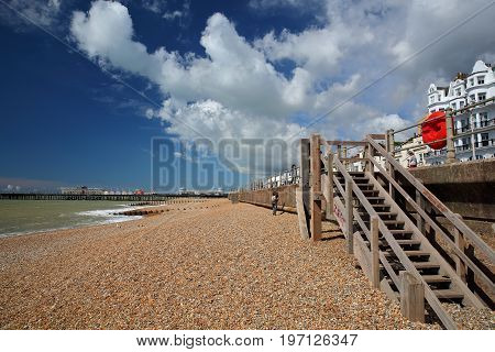 HASTINGS, UK - JULY 23, 2017: The colorful beach with the Pier (rebuilt and open to public in 2016) in the background and a blue sky with nice clouds