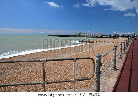 The colorful beach of Hastings with the Pier (rebuilt and open to public in 2016) in the background and a blue sky with nice clouds, Hastings, UK
