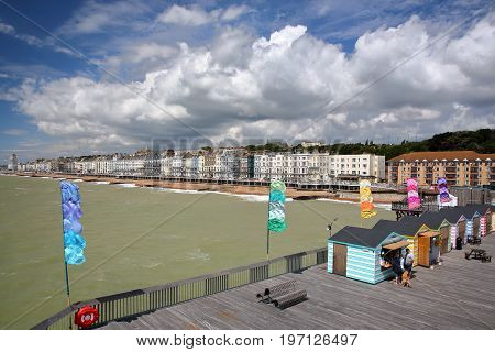 HASTINGS, UK - JULY 23, 2017: View of the seafront from the Pier (rebuilt and open to public in 2016) with colorful huts in the foreground and a beautiful cloudy sky