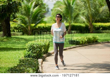 Portrait of cheerful Asian woman running during jogging workout in park on sunny day
