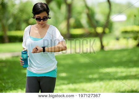 Portrait of healthy Asian woman checking fitness bracelet during  workout in park on sunny day