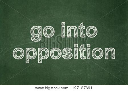 Political concept: text Go into Opposition on Green chalkboard background
