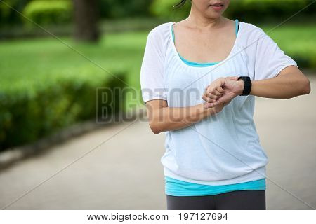 Mid section portrait of unrecognizable woman checking fitness watch during workout in park