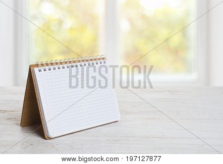 Notepad or calender on wooden table over blurred window background