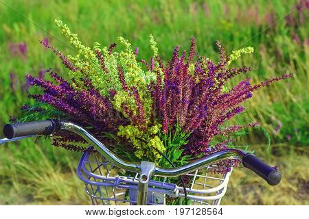 Bicycle with a bouquet of wildflowers in a basket in front of handlebar on a background of green grass in field