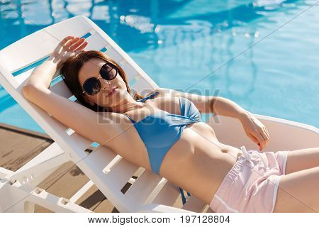 Laid-back weekend. Gorgeous slender young woman lying on a chaise longue near a swimming pool, holding hear hand behind her head and sunbathing
