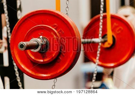 barbell with red plates for squats on monolift in gym