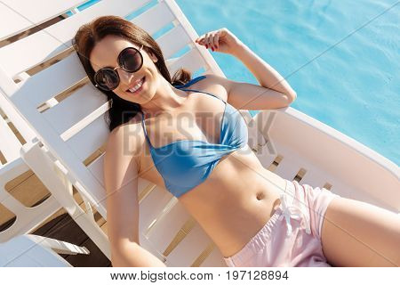 Enjoying sunshine. Pretty young woman in a blue bra and pink shorts sunbathing on a chaise longue near a swimming pool while smiling at the camera