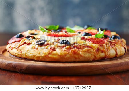 Rustic pizza with salami, tomatoes and black olives