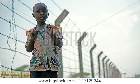 Lusaka Zambia - September 24 2014: African boy stands on a background of barbed wire along the railway