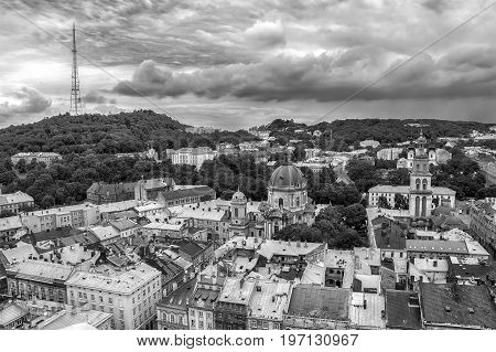 Lviv Ukraine old city vintage toned top view panorama with houses roofs. High Castle park Dominican Church Korniakt Tower Dormition Assumption church television tower Black and white