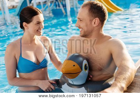 Quality time. Pleasant young man in a bird-shaped swim ring and his charming wife standing waist-deep in the swimming pool and talking to each other merrily